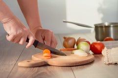 Händer som klipper morötter på en skärbräda Arkivfoton