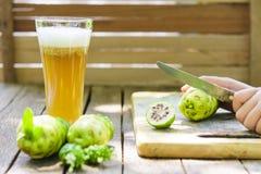 Händer som klipper noni, bär frukt på skärbräda- och nonifruktsaft på trätabellen Royaltyfri Bild