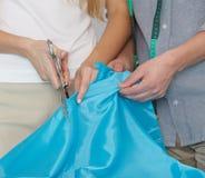 Händer som klipper tyg med sax Royaltyfri Foto