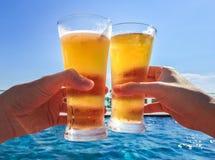 Händer som klirrar exponeringsglas av öl vid pölen Arkivfoto