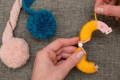 Händer som kretsar gult garn runt om Pom-Pom Maker royaltyfri bild