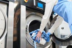 Händer som laddar tvätterit i tvagningmaskinen Royaltyfri Foto