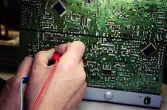 Händer som mäter den elektriska strömkretsen Den första Person View arkivbild