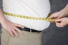 Händer som mäter magen av den sjukligt feta mannen Royaltyfri Bild