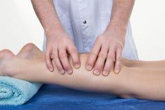 Händer som masserar den mänskliga kalvmuskeln Terapeut som applicerar tryck på det kvinnliga benet Arkivbild