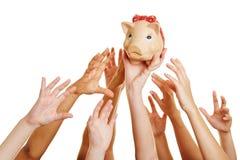 Händer som når för pengar i spargrisen Arkivbilder
