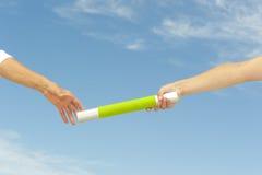 Händer som ner taktpinnen för teamwork arkivbild