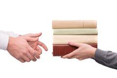 Händer som passerar högen av böcker Arkivfoto