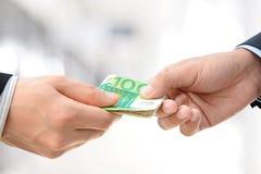 Händer som passerar pengar - räkningar för euro (EUR) Arkivfoto