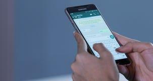 Händer som pratar med Whatsapp app på smartphonen arkivfilmer