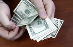 Händer som räknar dollar royaltyfria foton