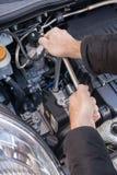 Händer som reparerar en bilmotor med en skiftnyckel royaltyfri bild