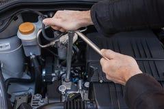Händer som reparerar en bilmotor med en skiftnyckel royaltyfria foton
