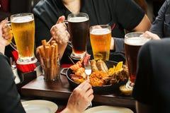 Händer som rymmer ölexponeringsglas som tillsammans dricker i baren Arkivbild