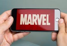Händer som rymmer Apple iPhone 6 med Logo Of Brand Marvel Arkivfoto
