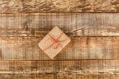 Händer som rymmer asken för hantverkpappersgåva arkivbild