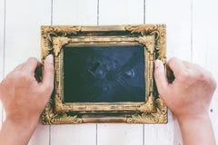 Händer som rymmer bildramen på träbakgrund arkivfoto
