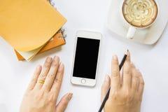 Händer som rymmer blyertspennan och smartphonen med anteckningsboken och kaffe på isolerat Royaltyfria Foton