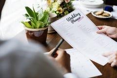Händer som rymmer bröllopstadsplaneraren Checklist Information Preparation arkivfoto
