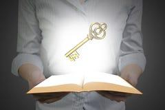 Händer som rymmer den öppna boken med guld- eurosymbol Royaltyfri Bild