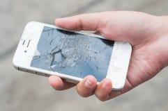 Händer som rymmer den brutna smartphonen Arkivbild