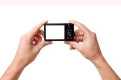 Händer som rymmer den digitala fotokameran Arkivbilder