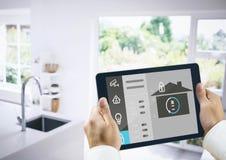 Händer som rymmer den digitala minnestavlan med symboler för hem- säkerhet Fotografering för Bildbyråer