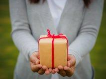 Händer som rymmer den härliga gåvaasken, kvinnlig geende gåva royaltyfri foto