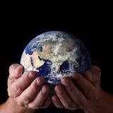 händer som rymmer den hållbara världen Arkivbild
