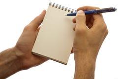 händer som rymmer den isolerade male blockpennan vit Royaltyfri Bild