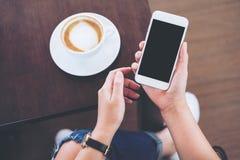 Händer som rymmer den vita mobiltelefonen med mellanrumssvartskärmen med kaffekoppen på trätabell- och golvbakgrund Royaltyfri Foto