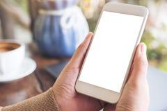 Händer som rymmer den vita mobiltelefonen med den tomma skrivbords- skärmen med bärbar dator- och kaffekoppen på tabellen i kafé Royaltyfria Foton