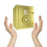 Händer som rymmer det guld- kassaskåpet Royaltyfri Foto