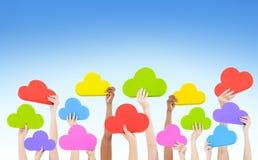 Händer som rymmer det mång- färgade molnet format arkivfoton