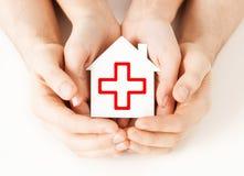 Händer som rymmer det pappers- huset med Röda korset Royaltyfri Bild
