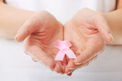 Händer som rymmer det rosa bröstcancermedvetenhetbandet Royaltyfri Bild