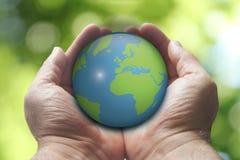 Händer som rymmer earth fotografering för bildbyråer