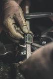 Händer som rymmer en digital klämma och mäter avståndet mellan två skruvar Royaltyfria Foton