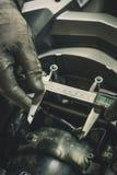 Händer som rymmer en digital klämma och mäter avståndet mellan två skruvar Arkivbild