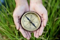 Händer som rymmer en gammal kompass Royaltyfria Foton