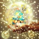 Händer som rymmer en genomskinlig boll med en julgran Arkivfoto