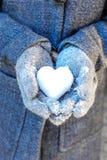 Händer som rymmer en hjärta av snö Royaltyfri Foto