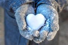 Händer som rymmer en hjärta av snö Royaltyfria Foton