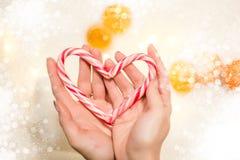 Händer som rymmer en hjärta gjord av en julgodis arkivbilder