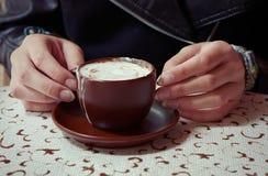 Händer som rymmer en kopp av caffemockan Royaltyfri Bild