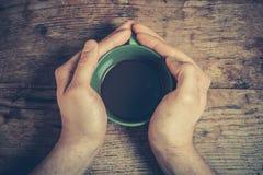 Händer som rymmer en kopp kaffe royaltyfri fotografi
