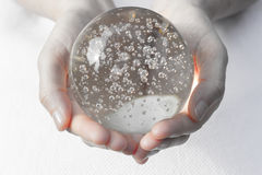 Händer som rymmer en kristallkula royaltyfri bild