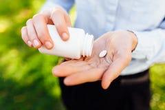 Händer som rymmer en krus med piller, closeup royaltyfria bilder
