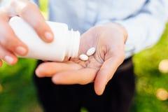 Händer som rymmer en krus med piller, closeup royaltyfria foton
