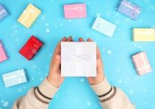 Händer som rymmer en liten ask med en gåva royaltyfria bilder